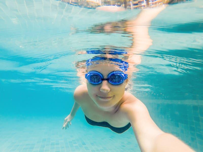 Une femme avec les verres de plongée nage dans la piscine sous l'eau photographie stock