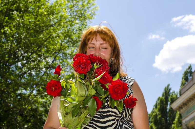 Une femme avec les yeux fermés sent un bouquet parfumé des fleurs photographie stock
