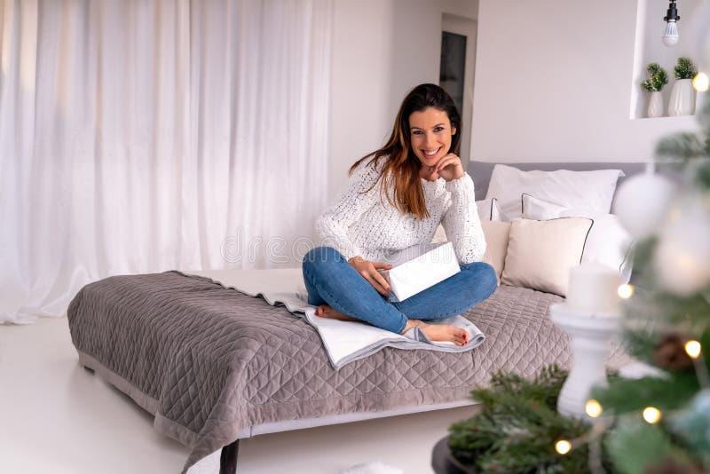 Une femme avec un cadeau de Noël assise sur le lit à côté d'un sapin de Noël image libre de droits
