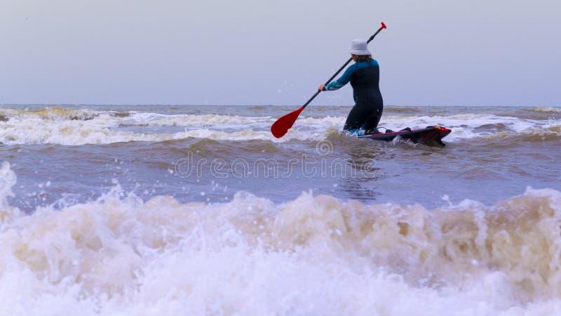 Une femme avec un chapeau sur la tête, la palette de pratique de support, sur la Mer du Nord aux Pays-Bas avec de grands vagues  photographie stock libre de droits