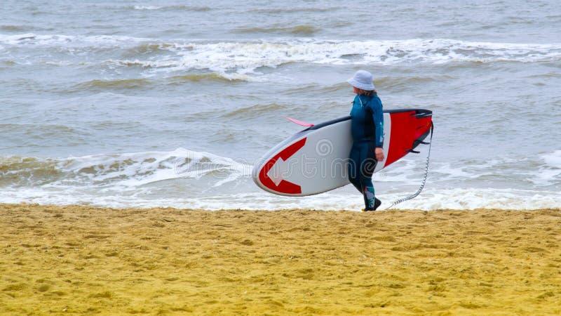 Une femme avec un chapeau sur la tête, la palette de pratique de support, sur la Mer du Nord aux Pays-Bas avec de grands vagues  photo libre de droits