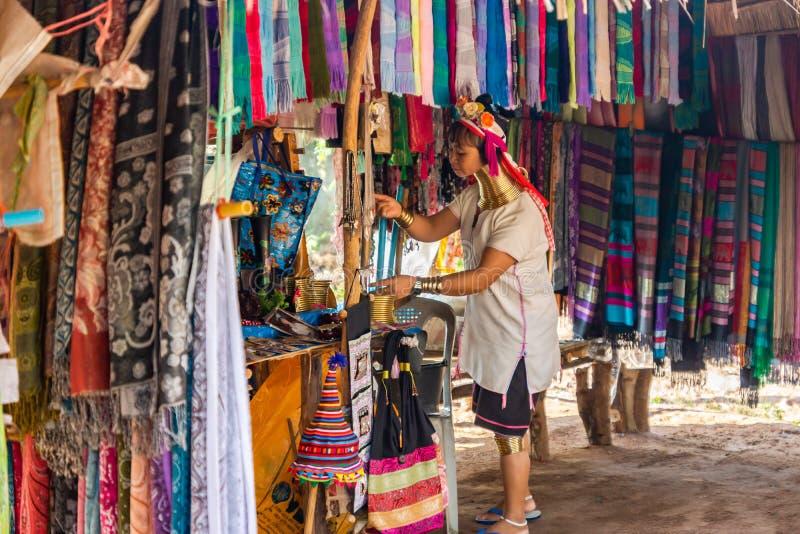 Une femme avec un long cou et des anneaux sur elle prépare un compteur pour la vente des écharpes en soie photo stock
