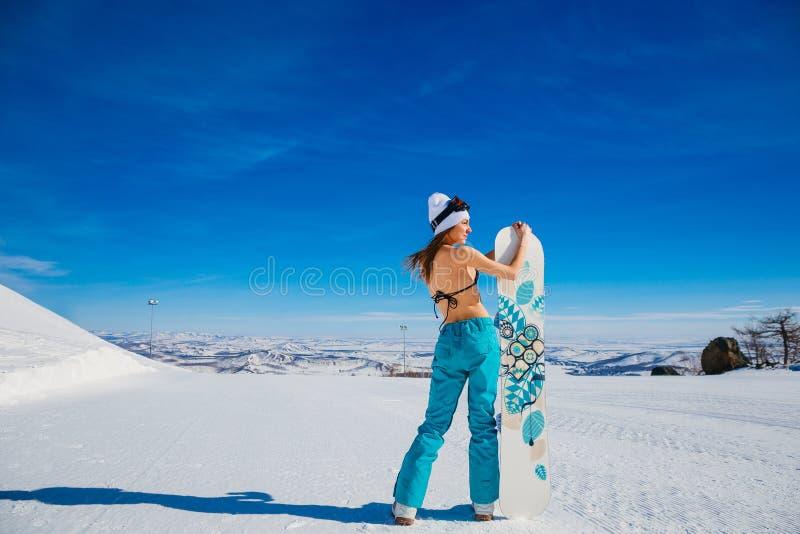Une femme avec un nu avec un surf des neiges recule avec elle de nouveau à la caméra pendant l'hiver dans les montagnes photographie stock libre de droits