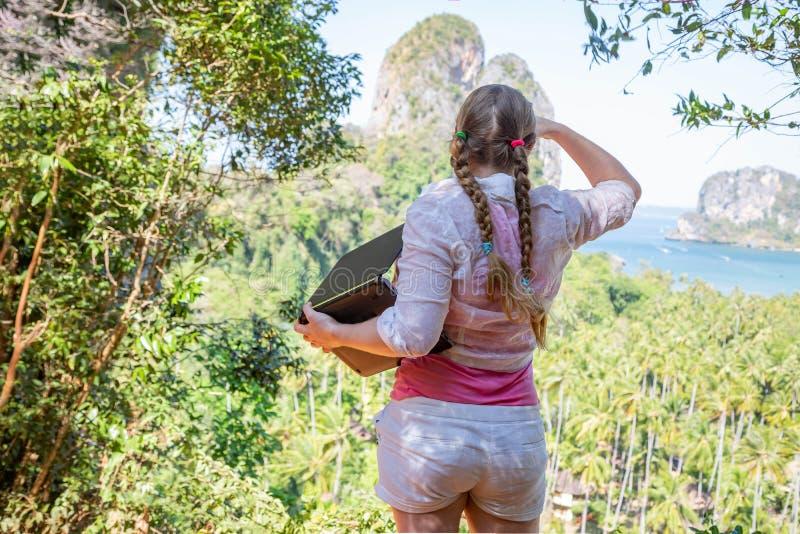 Une femme avec un ordinateur portable en haut des examinations de montagne la distance Le travailleur d'industrie du tourisme pré images libres de droits