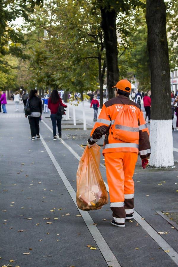 Une femme avec un paquet nettoie la rue des débris Russie, Krasnodar, octobre 7,2018 photographie stock