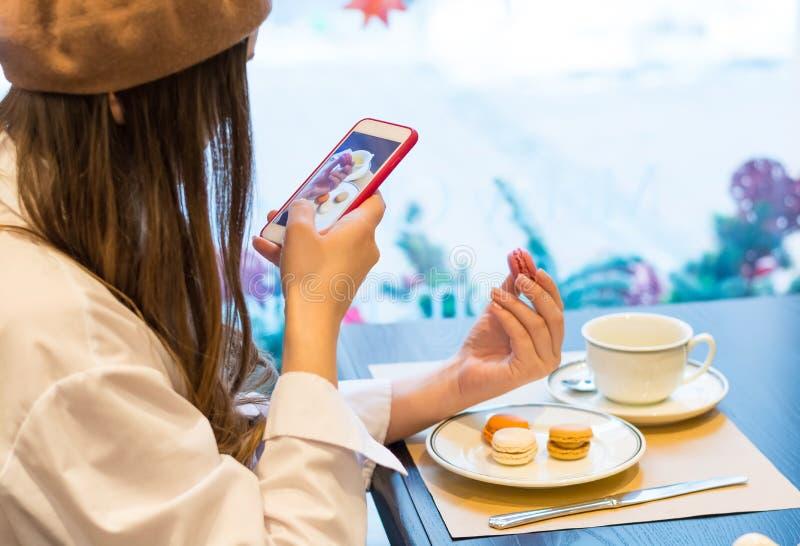 Une femme avec un smartphone prend à une image de des macarons et une tasse de thé dans un café photographie stock