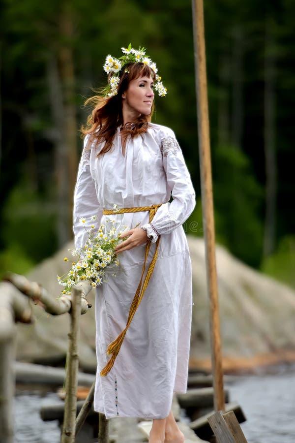Une femme avec une guirlande des fleurs à l'eau photos stock