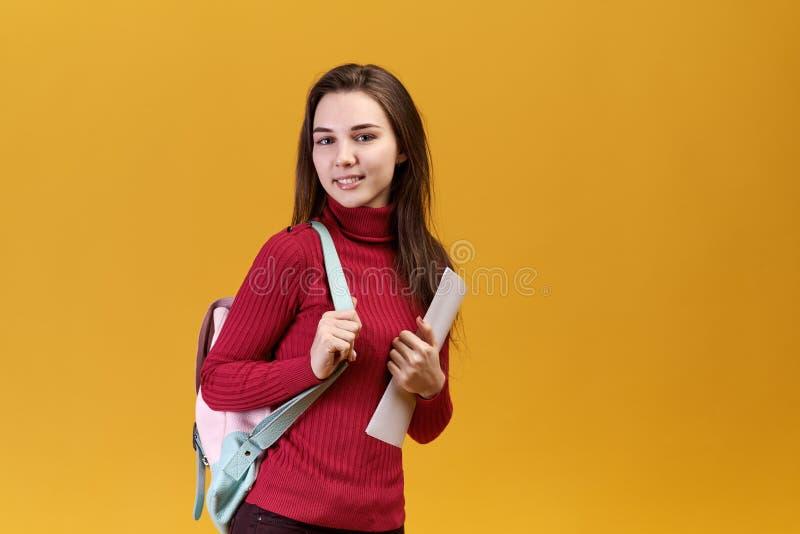 Une femme belle a une expression joyeuse, regarde les yeux gris brillants juste vous, utilisant un chandail rouge photo libre de droits