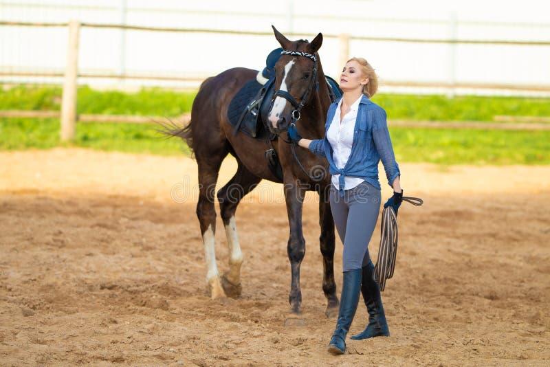 Une femme blonde avec un cavalier de jockey à cheveux longs sur un cheval de la baie, dans un paddock sur un ranch images stock