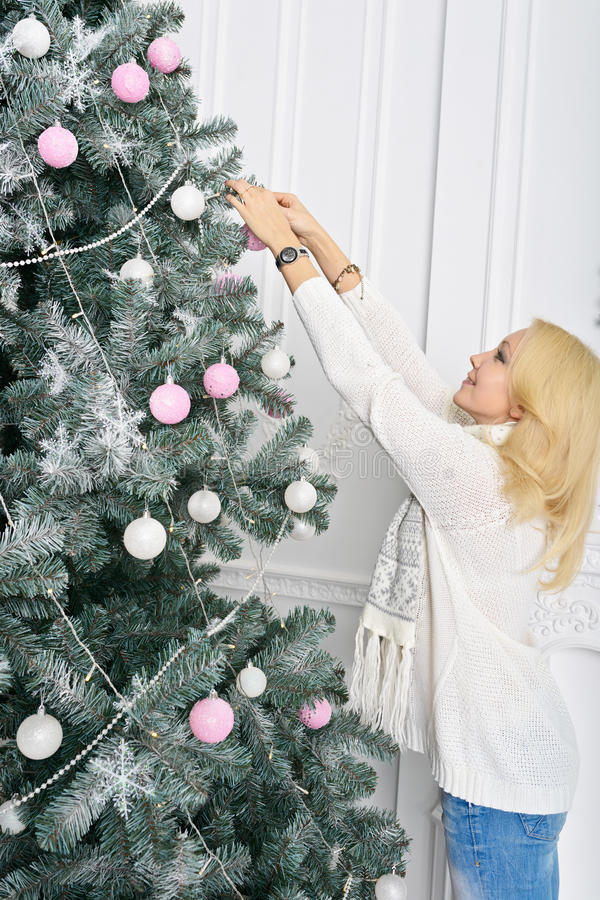 Une femme blonde déroulant la nouvelle année coloré emballée se présente photos libres de droits