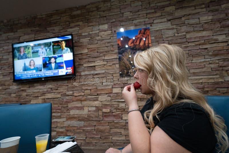 Une femme blonde mange son petit déjeuner gratuit d'hôtel observant de fausses actualités sur TV par câble images libres de droits
