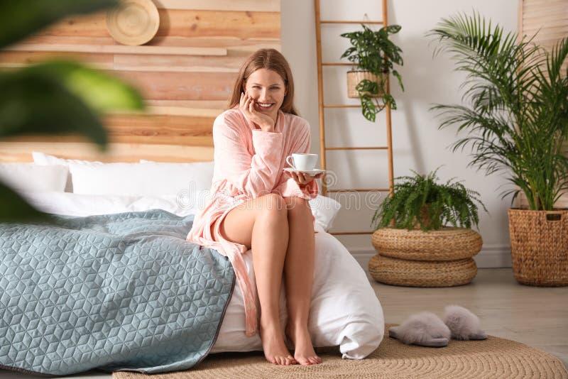 Une femme boit du café dans la chambre à coucher avec des plantes Idées de conception maison photo libre de droits