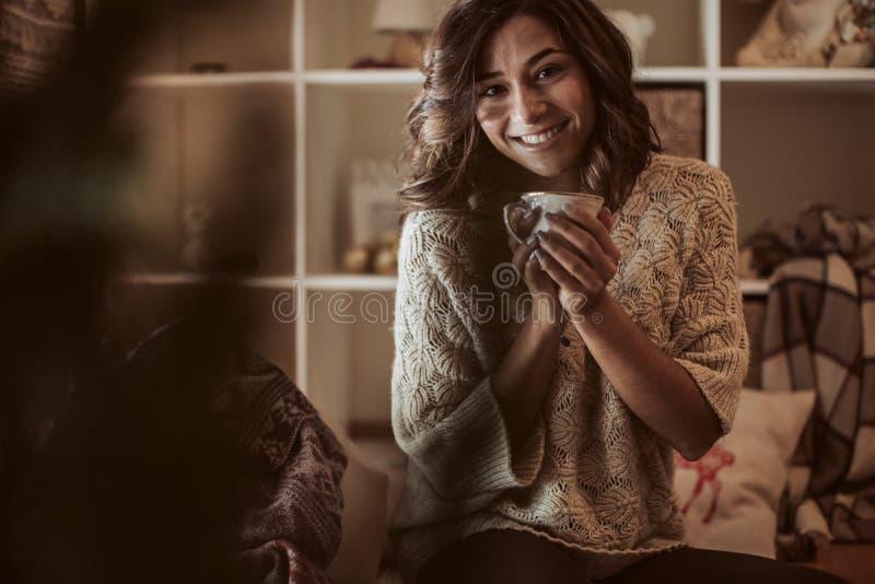 Une femme boit une tasse de thé à la maison - Noël images stock