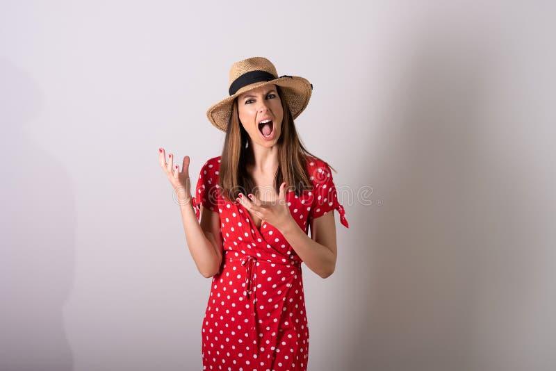 Une femme bouleversée dans une robe rouge se tenant dans un studio image libre de droits