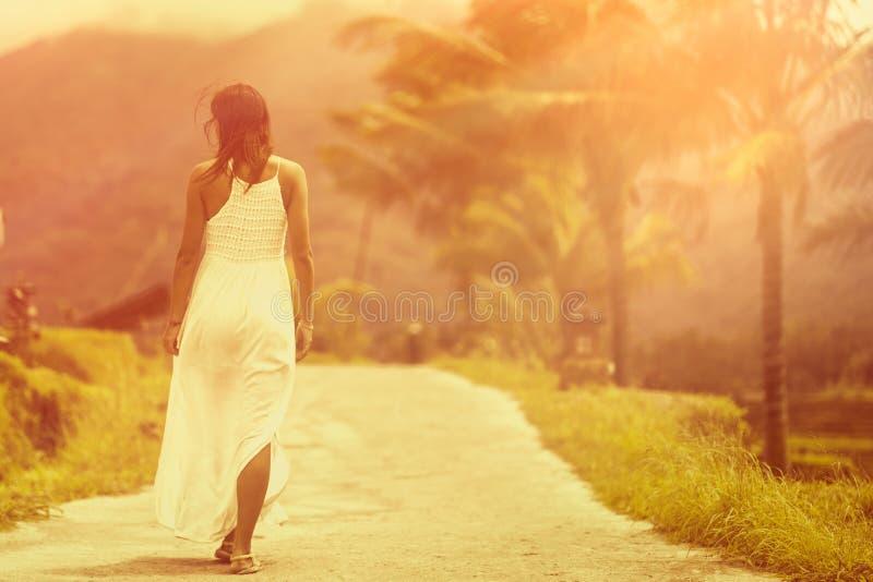 Une femme bronz?e dans une robe blanche marche en avant sur la route La vue du dos Dans le fond, une montagne et des palmiers photo stock