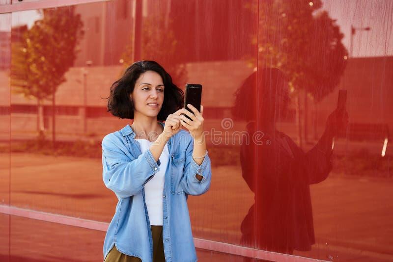Une femme brunette en T-shirt blanc et chemise en denim avec un mur rouge derrière, tient un smartphone dans la main photographie stock