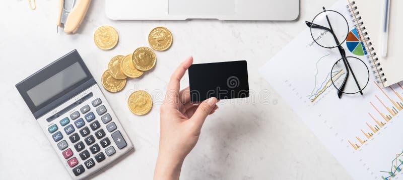Une femme calcule les honoraires, bénéfice et fait un paiement en ligne sur une table de marbre moderne de bureau, fausse, vue su photo stock
