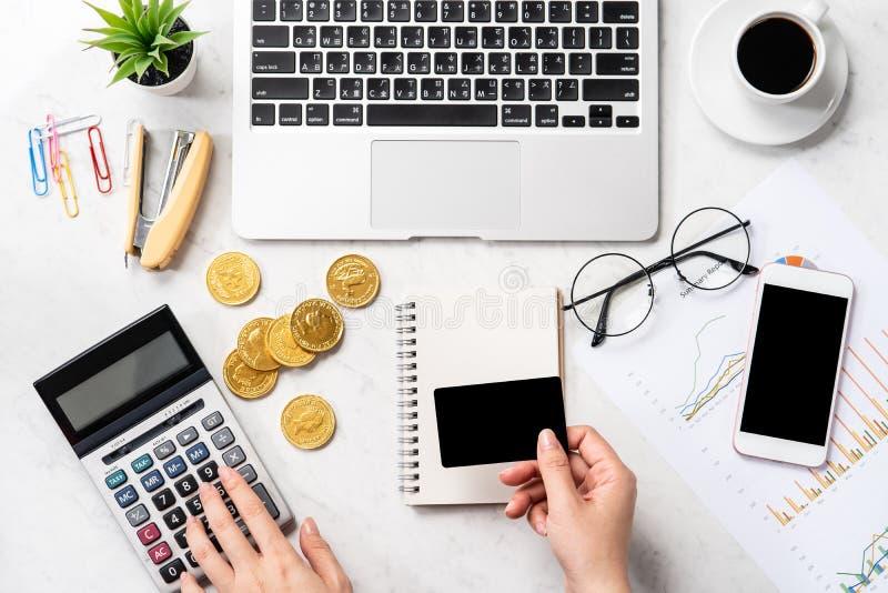 Une femme calcule les honoraires, bénéfice et fait un paiement en ligne sur une table de marbre moderne de bureau, fausse, vue su photo libre de droits
