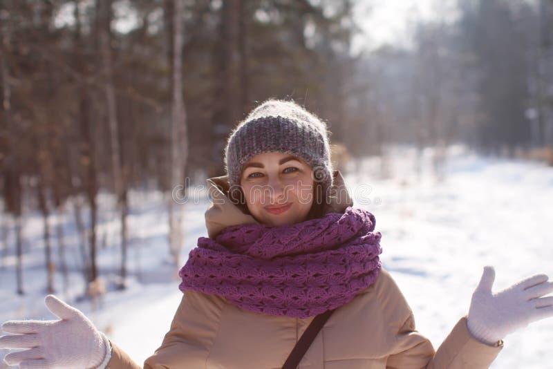 Une femme caucasienne satisfaite marche en parc d'hiver Jeune femme contre un parc couvert de neige un jour ensoleillé photos libres de droits