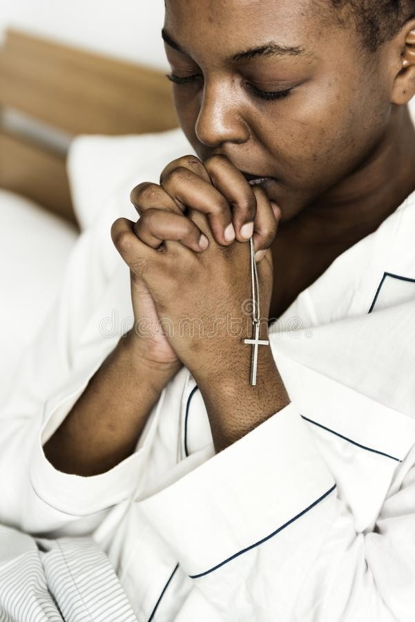 Une femme chrétienne priant dans le lit photographie stock libre de droits