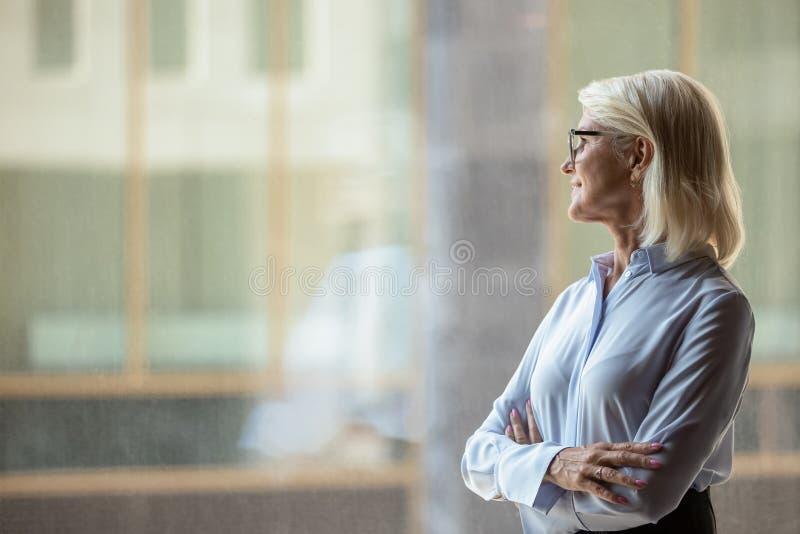 Une femme d'affaires d'âge moyen regarde à distance la pensée ou la visualisation photo stock