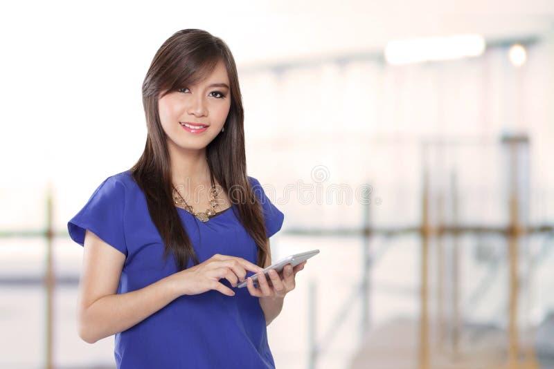 Une femme d'affaires asiatique prospère utilisant un gadget mobile photo stock