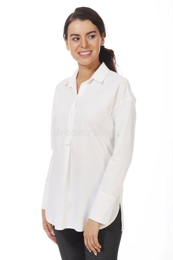 Une femme d'affaires brunette dans un blouse officiel blanc avec des ruches près photo photo stock