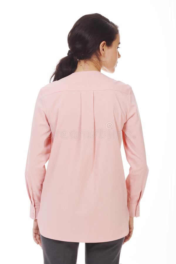 Une femme d'affaires brunette dans un blouse officiel rose avec des ruches près photo photos stock