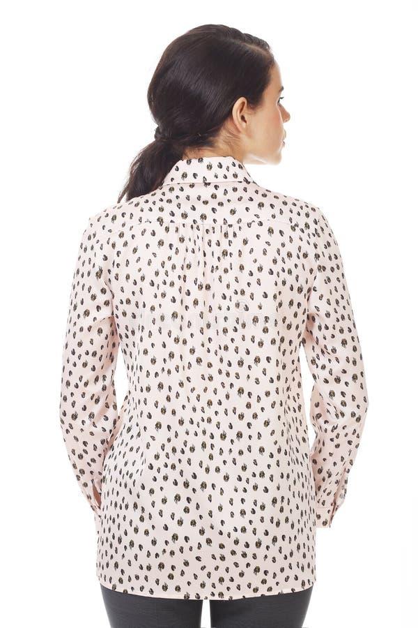 Une femme d'affaires brunette dans un blouse officiel rose avec des ruches près photo photo stock