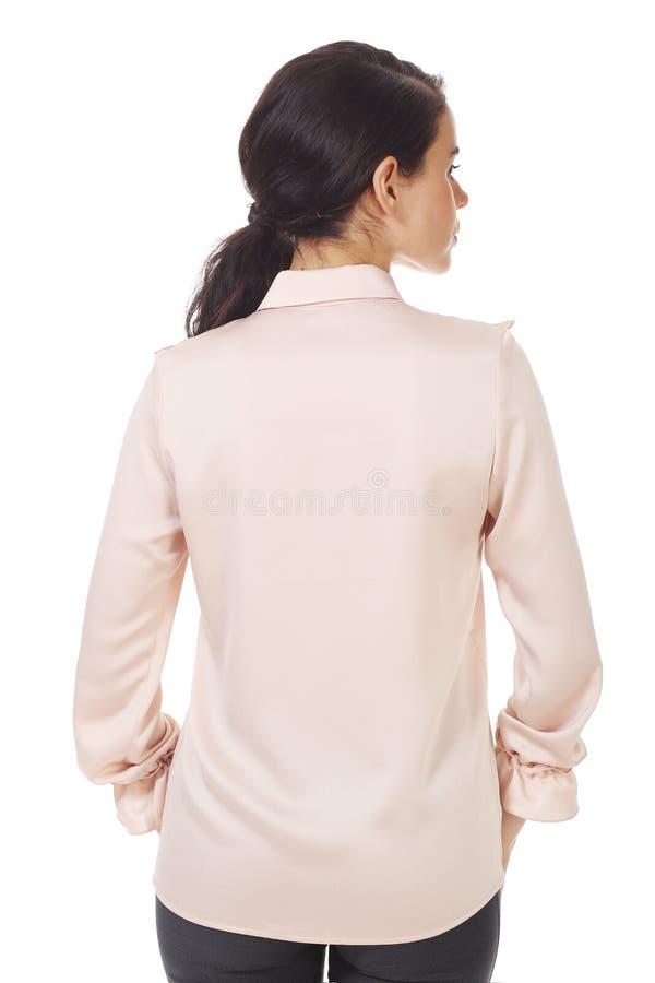 Une femme d'affaires brunette dans un blouse officiel rose avec des ruches près photo images stock