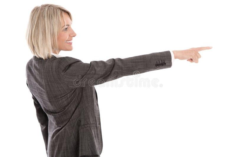 Une femme d'affaires d'isolement plus âgée ou mûre se dirigeant avec le doigt photo stock