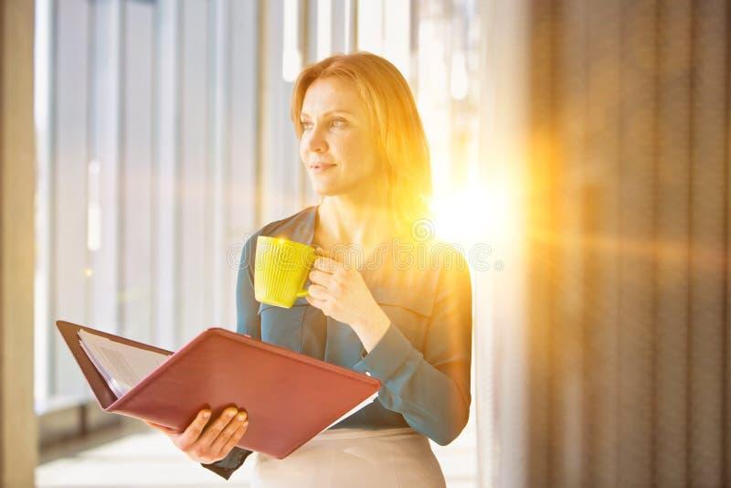 Une femme d'affaires en train de lire un fichier pendant qu'elle boit du café au bureau avec la lentille jaune en arrière-plan photographie stock libre de droits