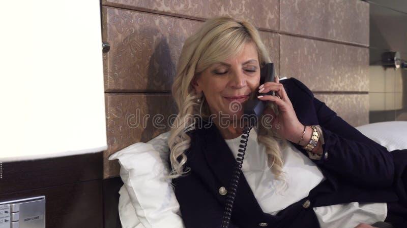 Une femme d'affaires fait appel au téléphone dans une chambre d'hôtel image stock