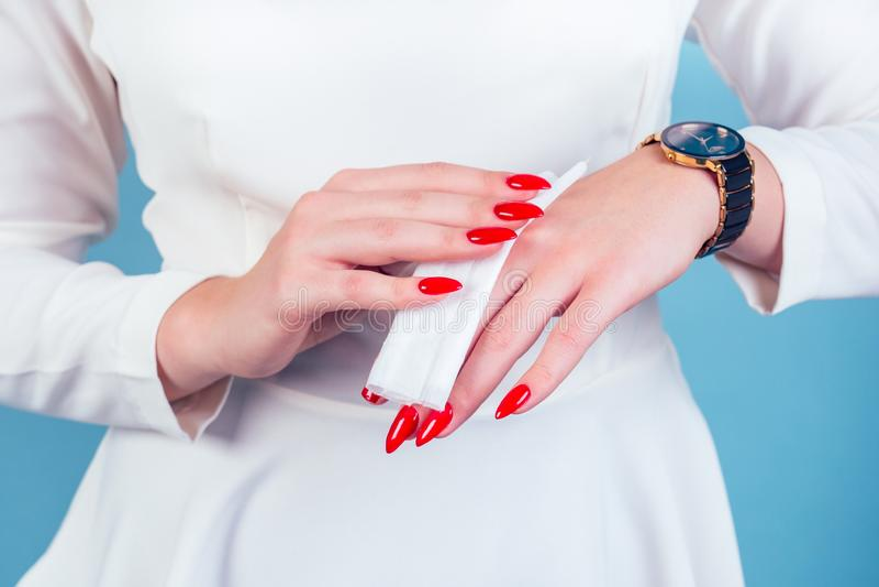 Une femme d'affaires se serrant les mains avec une serviette mouillée serrant les ongles rouges et longs manucure sur fond bleu e photo stock