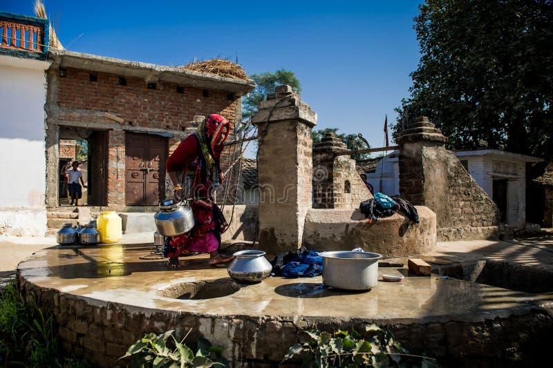 Une femme d'Inde lave ses vêtements près d'un puits de public photographie stock libre de droits