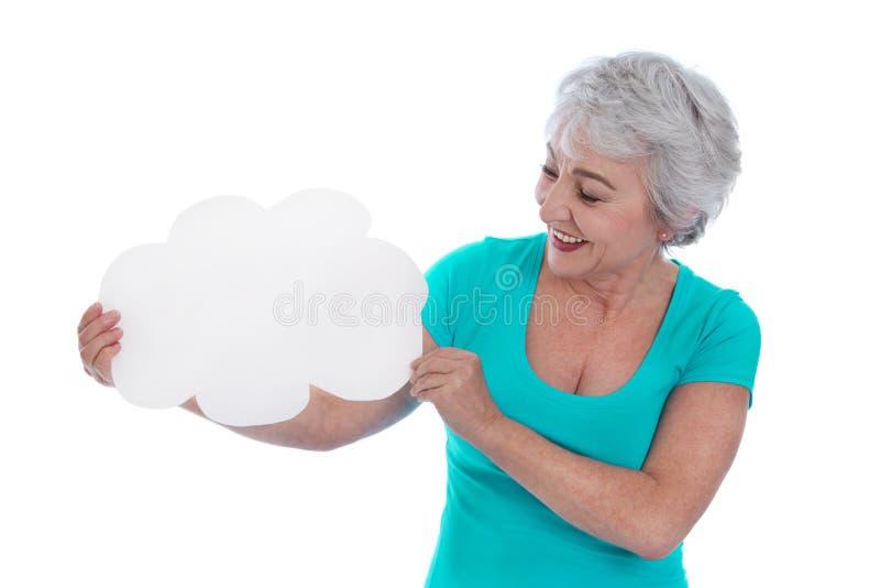 Une femme d'isolement plus âgée tenant un connexion blanc ses mains. image libre de droits
