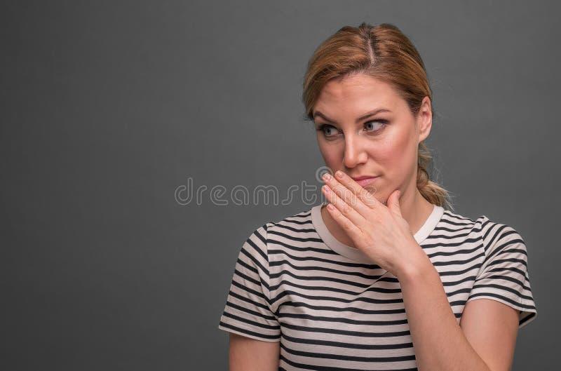 Une femme d?peint le m?pris du bavardage ou le m?contentement sur un fond gris images libres de droits