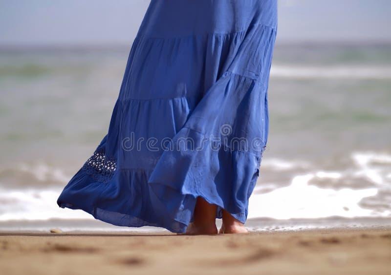 Une femme dans une longue jupe bleue se tient sur la plage photographie stock libre de droits
