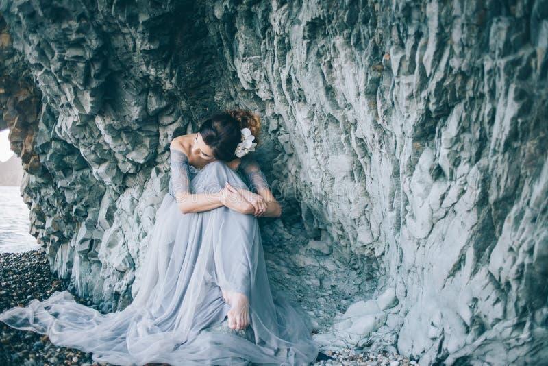 Une femme dans une longue robe se reposant près de la mer photographie stock libre de droits