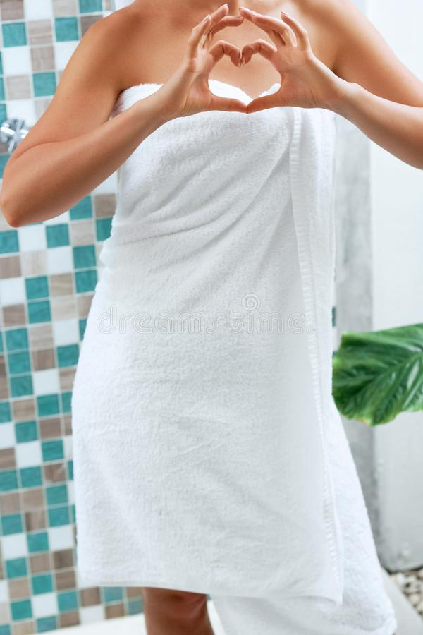 Une femme dans un bain avec la serviette La fille montre des mains au coeur de forme images libres de droits
