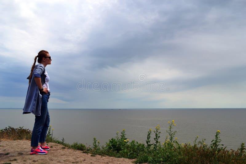 Une femme dans un capot regarde la mer photos libres de droits