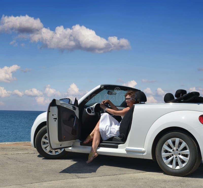 Une femme dans un convertible blanc photo stock