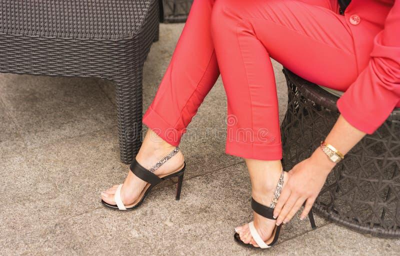 Une femme dans un pantsuit que la couleur du corail vivant se repose dans une chaise et redresse le fermoir sur des sandales images stock