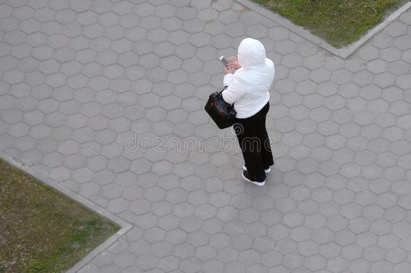 Une femme dans une veste blanche et un pantalon noir tient un sac et un téléphone dans sa main Vue d'en haut, rue, route comme fl photo libre de droits
