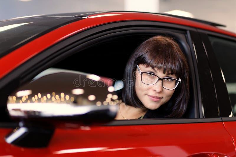 Une femme de brune regarde hors d'une fenêtre de voiture photo stock