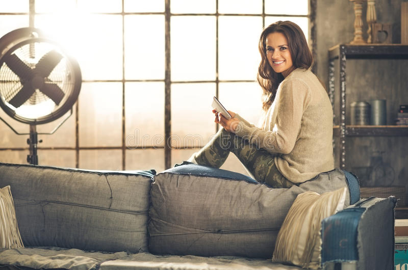 Une femme de brune s'asseyant sur un sofa de retour photos libres de droits