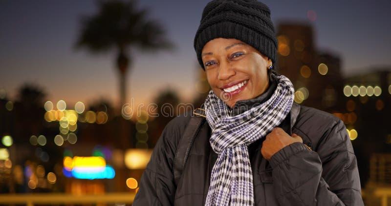 Une femme de couleur plus âgée dans des vêtements chauds du centre la nuit photo libre de droits
