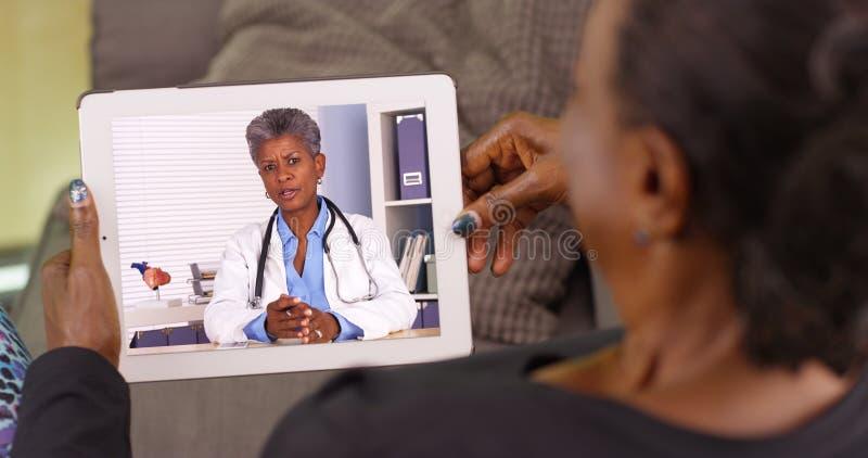 Une femme de couleur plus âgée parlant à son docteur d'Afro-américain par l'intermédiaire de la causerie visuelle image libre de droits