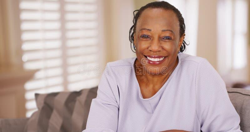 Une femme de couleur plus âgée regarde heureusement l'appareil-photo photo libre de droits