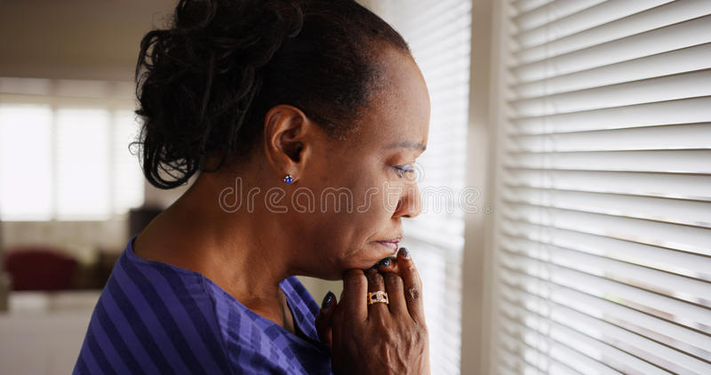 Une femme de couleur plus âgée regarde tristement sa fenêtre image stock
